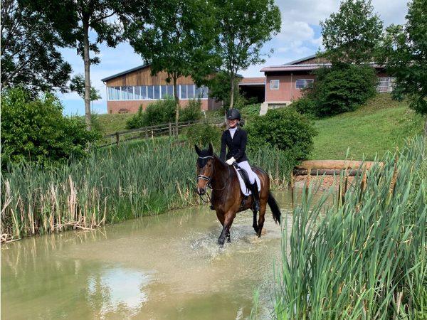 Kim Kubla reitet mit Pferd Fritzi durch den Wassergraben